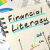 Financial Literacy written on a notepad sheet.